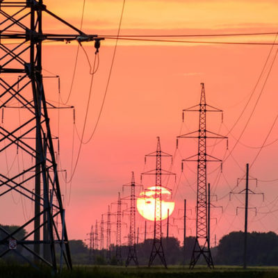 power lines and towers with sunset in the distance
